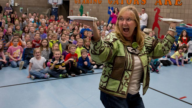 Kindergarten teacher Karyn Alley holds two whipped-cream pies Thursday, March 19, at Gearing Elementary School in St. Clair. The students were rewarded with the pie-throwing event for raising more than $1,400 with box tops.