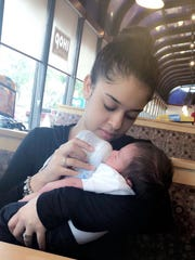 Betsy Soto, 18, feeding her 8-week-old nephew, Aiden