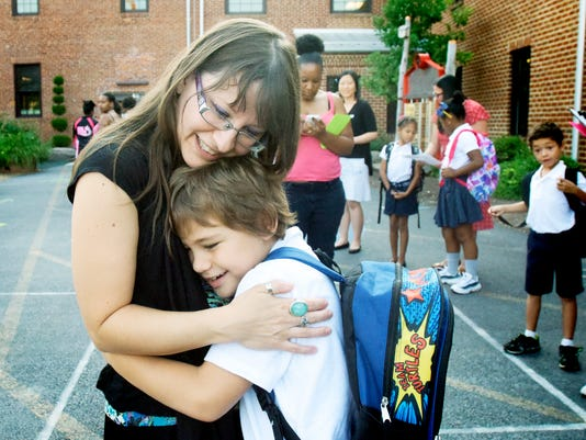Michelle Van Dyke of York City hugs her second-grader son Niles during the first day of classes at York Academy Regional Charter School Monday, August 17, 2015. The K-6 academy adds a grade each year with the goal of becoming K-12. This is the school's fifth year of operation. Bill Kalina - bkalina@yorkdispatch.com