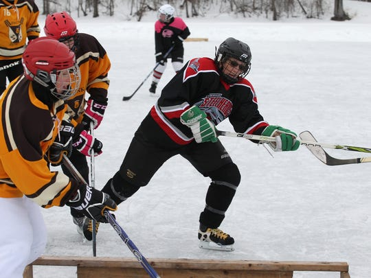 Cathy Westberg, center, of Wausau fights for the puck in front of her team's goal Saturday at Sunny Vale Park in Wausau during the first of three weekends of Badger State Winter Games action. She plays on a team of local women called the Hericanes.