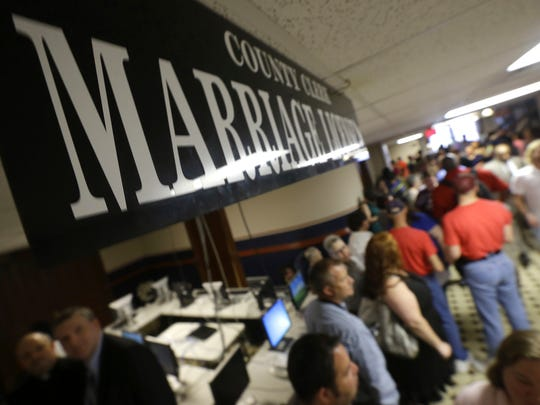 In this May 12, 2014, file photo, couples line up to file paperwork for marriage licenses at the Pulaski County Courthouse in Little Rock, when the state's largest county began issuing marriage licenses for same-sex couples.