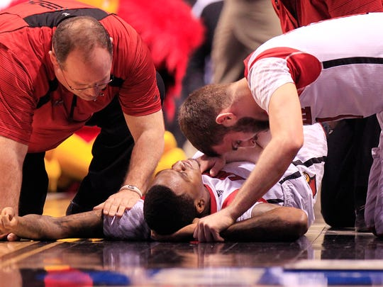 Louisville player Luke Hancock, right, tries to comfort teammate Kevin Ware after Ware broke his leg against Duke March 31 2013 at Lucas Oil Stadium.