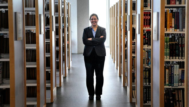 Karen Pundsack stands surrounded by books May 13 at the St. Cloud Public Library. Pundsack was recently named executive director of the Great River Regional Library by the library's Board of Trustees. She has been serving as interim director since July 2014.