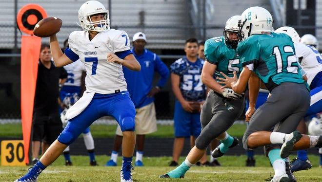 Sebastian River quarterback Shea Spencer looks to pass Thursday, Sept. 28, 2017, under pressure from the Jensen Beach defense during their high school football game at Jensen Beach High School.
