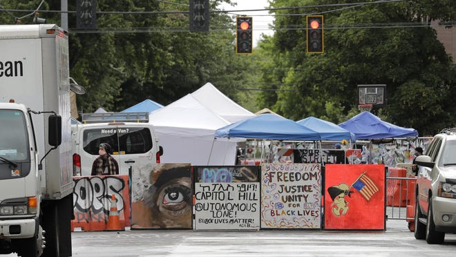 Signs are seen at an entrance Monday to what has been named the Capitol Hill Occupied Protest zone in Seattle. Protesters have taken over several blocks near downtown Seattle after officers withdrew from a police station in the area following violent confrontations.