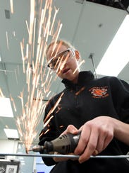 Sparks fly as Natalie Corrigan uses a Dremel tool to