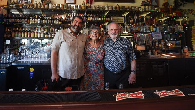New Tower of London owner Kevin Cyr, left, with former owners Heidi and Ralph Meyer at the popular Tumon pub on Dec. 19, 2017.