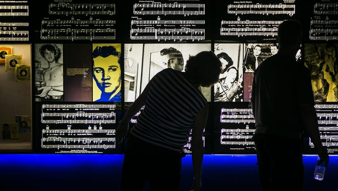 Candace Wilson, left, and Brad Flory, of Mason, Mich., look at photos of Elvis Presley during a tour of the Mississippi River Museum at Mud Island River Park on Aug. 12, 2017.