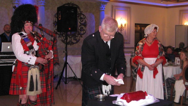 """Left to right, Janet Auster Whalen, pipemaster of the Amerscot Pipe Band, Graham Smythe, who is about to address the haggis, and Leslie Urbanski as """"Posie Nancy"""" are shown during a past Robert Burns Supper."""