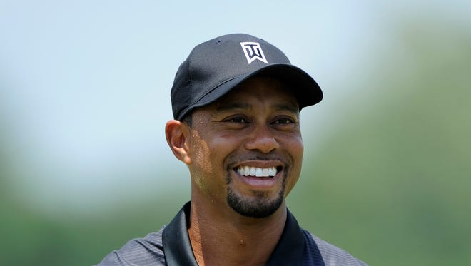 Tiger Woods smiles on the driving range during a practice round for the Quicken Loans National golf tournament Tuesday in Bethesda, Md. (AP Photo/Nick Wass)