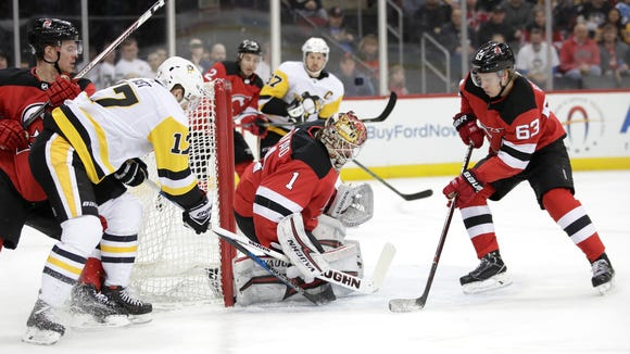 New Jersey Devils goalie Keith Kinkaid (1) stops a shot by Pittsburgh Penguins right wing Bryan Rust (17) during the first period of an NHL hockey game Saturday, Feb. 3, 2018, in Newark, N.J. (AP Photo/Julio Cortez)