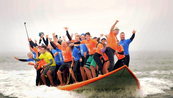 Sixty-six surfers react as they set a Guinness World Record for most riders on a board, as they stand on the 1,100 pound, 42-foot board in Huntington Beach, Calif., Saturday, June 20, 2015.