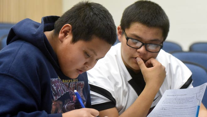 Tsé Bit'a'í Middle School eighth grader Shaun Barber, left, gets help on homework from his brother, Shiprock High School junior Shane Barber, on Thursday at the middle school in Shiprock.