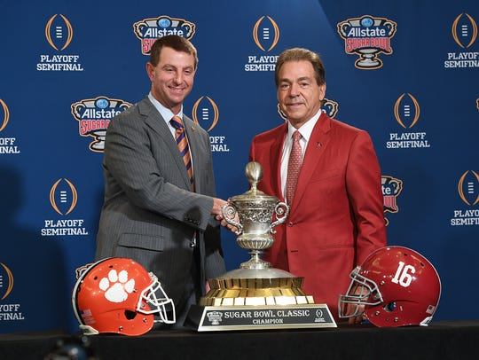 Clemson head coach Dabo Swinney, left, shakes hands