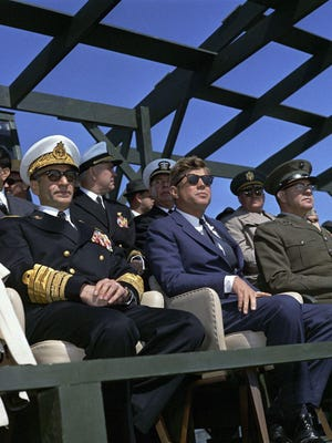 President John F. Kennedy (center, wearing sunglasses), Mohammad Reza Pahlavi, the Shahanshah of Iran (left of President Kennedy) and other distinguished guests watch a demonstration of U. S. Navy and Marine Corps amphibious landing operations at Onslow Beach from Riseley Pier, Camp Lejeune, North Carolina. The Shahanshah, in the United States on a state visit, joined the President in North Carolina to inspect the U.S. Atlantic Fleet. Also pictured to the President's left is the Commandant of the Marine Corps General David M. Shoup.