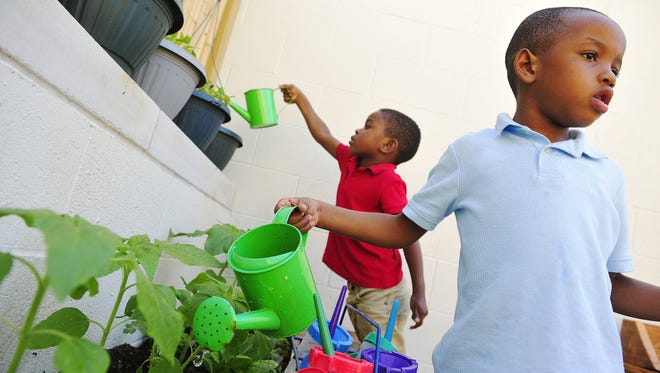 Michael Holt, left, and Ricky Robinson water the garden as part of the pre-K program at Casa Azafran in Nashville.
