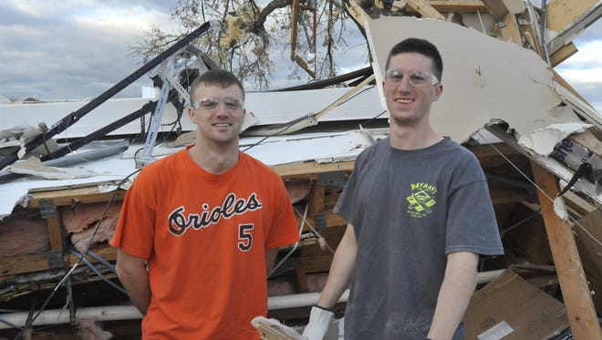 Kevin Grier, left, and Tom Routt, right, stand where they had been trapped after their townhouse on Scenic Highway was destroyed in Tuesday night's tornado.