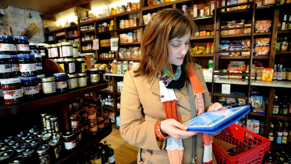 A young shopper uses her iPad to check a recipe while
