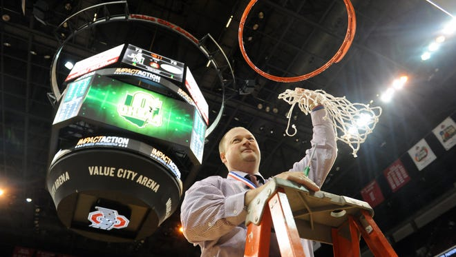 John Glenn head coach Greg Woodard cuts down the net after the Muskies claimed their first  basketball state championship in school history.