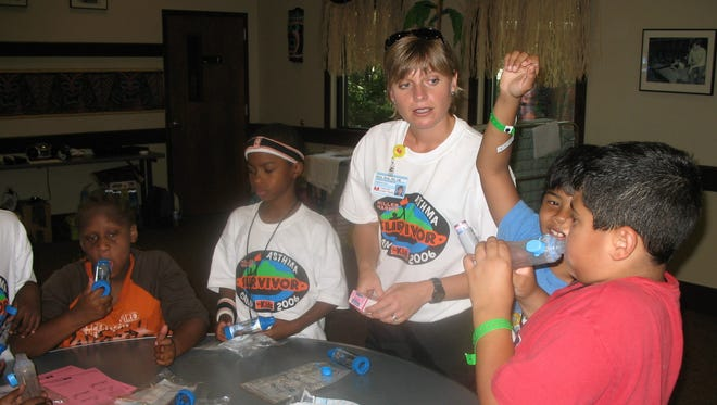 Registered nurse Alice Bray helps a group of children learn to use their asthma medications. The Joe C. Davis YMCA Outdoor Center in Antioch hosted the inaugural Miller Harris Asthma Camp for Kids in partnership with the Miller Harris Foundation and Monroe Carell Jr. Children's Hospital at Vanderbilt. At the outdoor center, 34 boys and girls from inner-city Nashville experienced the adventure of summer camp while learning keys to living with asthma, thanks to doctors, respiratory therapists and other caregivers from the children's hospital.