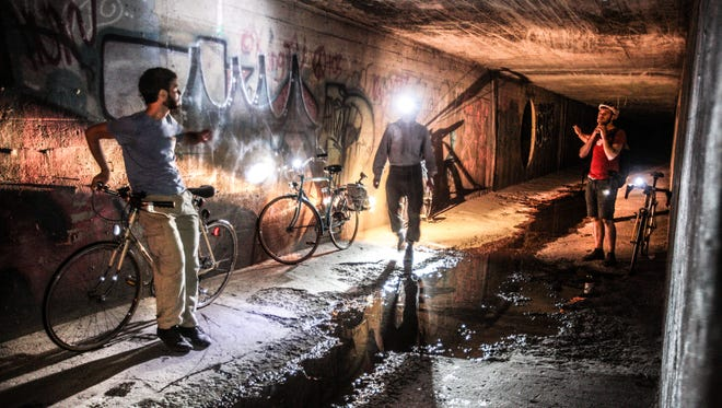 Wednesday September 4th, 2013, Indy Star Reporter Will Higgins and Photographer Michelle Pemberton adventure under the city via the Pogue's Run Tunnel with avid bicycle rider Jamey McPherson and French visiting artist Florian Riviere. Here expedition members look over graffiti at the end of the tunnel. (Michelle Pemberton/The Star)