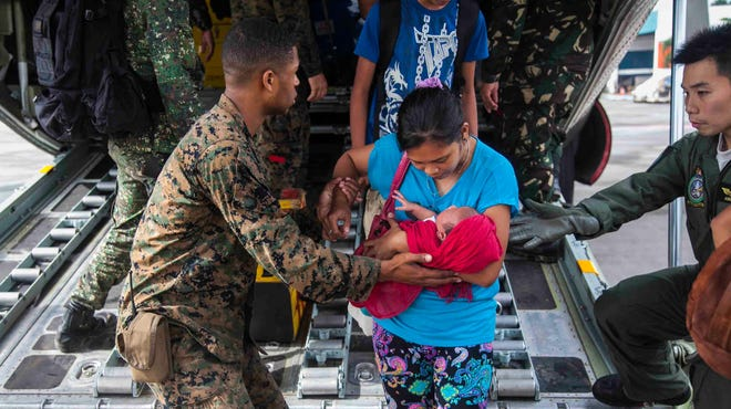 Marine Lance Cpl. Xavier Cannon helps civilians displaced by Typhoon Haiyan disembark from a C-130 aircraft at Villamor Air Base in the Philippines on Nov. 12.