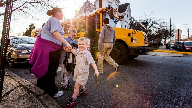 Tracy Carter-Parker picks up her children from the school bus at the corner of West Seventh Street and North Franklin Streets near Tilton Park on Tuesday afternoon.