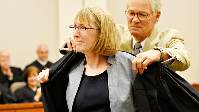 Judge Christy Fawcett is assisted with her robe by her husband, Rob Fawcett, after officially being sworn into office by York County President Judge Joseph C. Adams during a ceremony at the York County Judicial Center in York City Wednesday, July 20, 2016. Dawn J. Sagert photo
