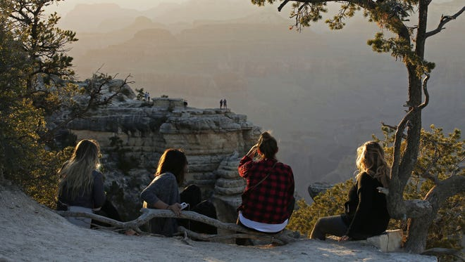 Tourists watch the sunset on Mather Point, South Rim at the Grand Canyon.