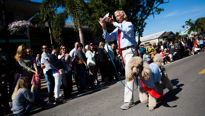 """Pete Gleeman and his dog Charlie Bear walk down Third Avenue South in their presidential costumes during the Pets on Third celebration on Sunday, Jan. 14, 2018, in downtown Naples. The 2018 theme for the Pet Parade was """"historical figures."""""""