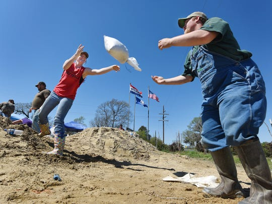 Lacey Owens, left, tosses a sandbag to Jonathan Mullenix, as the two Hebert residents pitch in to help provide bags to area residents to protect homes an property from rising floodwaters on Monday,