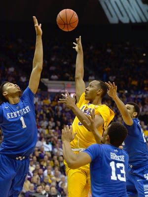 LSU guard Tim Quarterman (55) shoots in heavy traffic as Kentucky forward Skal Labissiere (1), Kentucky guard Isaiah Briscoe (13) and Kentucky guard Jamal Murray (23) defend in the second half of an NCAA college basketball game in Baton Rouge, La., Tuesday, Jan. 5, 2016. LSU won 85-67. (AP Photo/Bill Feig)
