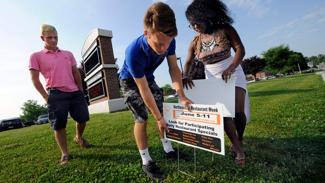 Students, from left, Ryan Shindler, Hayden Seifert and Shanbrea Wade, all 17, place signs advertising Restaurant Week along the road near Northeastern High School, Wednesday, June 1, 2016. John A. Pavoncello photo