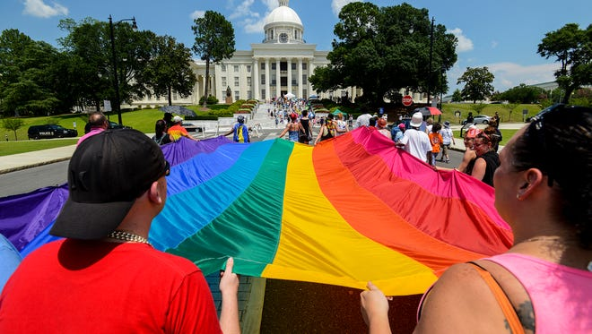 People carry the Pride flag to the Capitol during the Montgomery Pride march on Sunday, Jun. 26, 2016 in Montgomery, Ala.