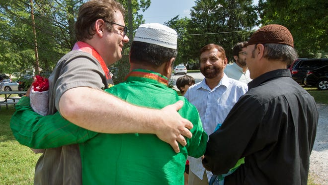 Rev. Christopher Rodkey, pastor of St. Paul's United Church of Christ in Dallastown, left, is greeted after a Muslim prayer marking Eid al-Fitr, or the end of Ramadan. Nearly 50 people came to Brookside Park in Dover Township to show their support for York County's Islamic community.
