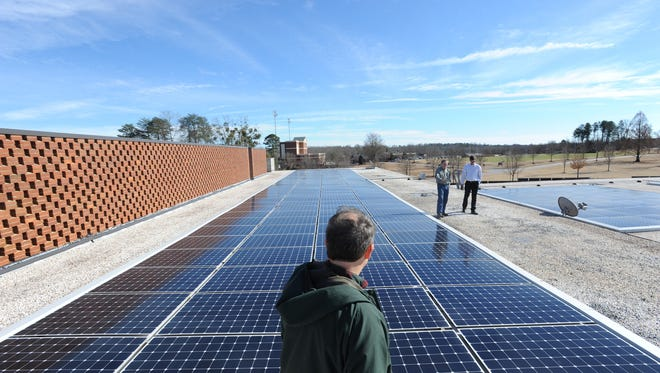 Jeff Redderson of Furman University walks along the roof of the Furman physical activity center where a large bank of solar panels sits. Wednesday, February 5, 2014.