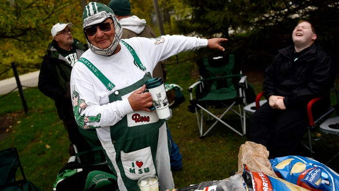 Merrill 'The Bird' Sheldon, left, of Eaton Rapids, laughs with his grandsons and friends while tailgating before Michigan State's game against Penn State on Saturday, November 4, 2017, in East Lansing.