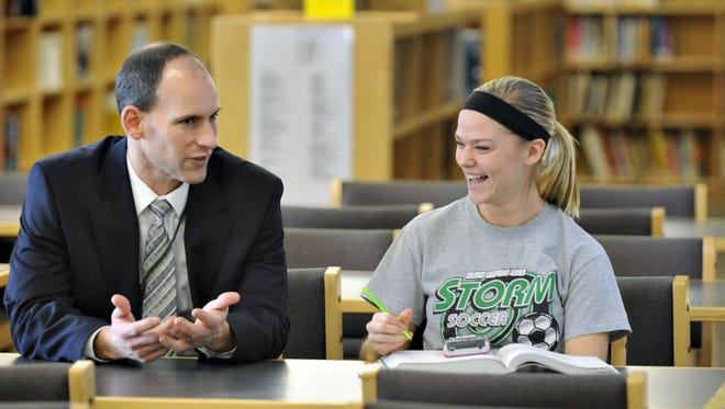 In this 2013 file photo, Sauk Rapids-Rice High School Principal Erich Martens gives Nina Jacobson a pep talk as she studies for her ACT test in the media center.