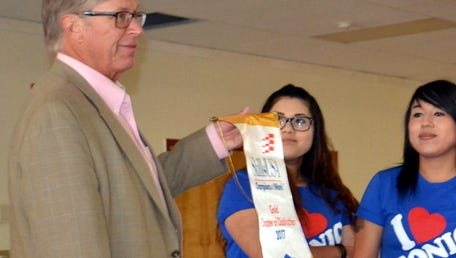 Deming High seniors Monica Barba and Karima Acosta, along with SkillsUSA Adviser Mary Anderson, presented Deming Public Schools Superintendent  Dr. Dan Lere with the Chapter of Excellence banners won at state competition.