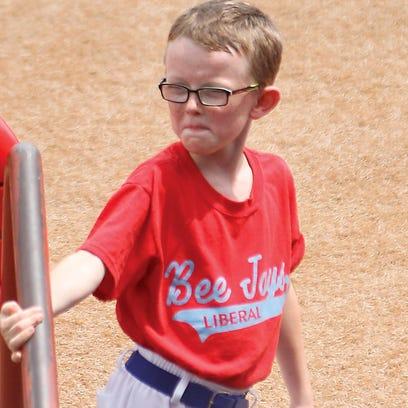 Bat boy Kaiser Carlile, 9, gets ready for a National