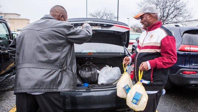 Norman Oliver (right) and his friend Tyrone Brown load turkeys into Brown's car at B.J.'s Wholesale Club in New Castle on Tuesday afternoon.