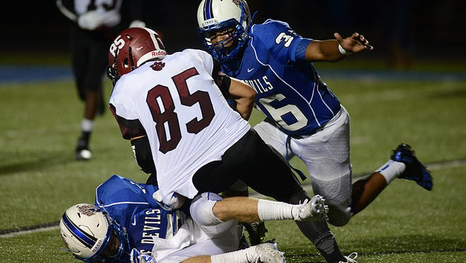 Zanesville's Ben Kaufman pulls down Newark's Parker Emerine as Zanesville's Leondre Crosby comes in to finish the tackle during their 2015 game at John D. Sulsberger Memorial Stadium. The Blue Devils' 20-17 comeback win, which required a late defensive stand, triggered a run to the Division III state semifinals.