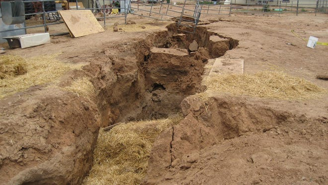 An earth fissure trapped a 1,200-pound horse in 2006 when it opened under a Chandler Heights corral. A monsoon thunderstorm expanded a small crack in the earth to create a huge gully, shown. The horse died after a 15-hour rescue attempt.