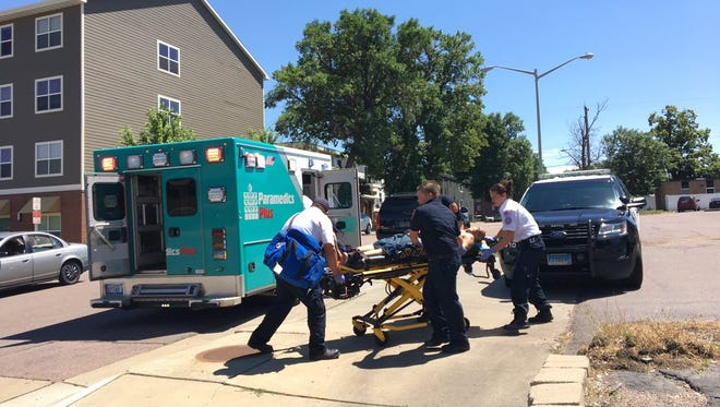 A man is loaded onto a stretcher after a reported stabbing near the 600 block of W. 11th Street in central Sioux Falls.