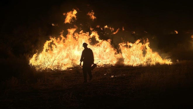 A firefighter in Santa Barbara County battles the Rey Fire, was 87 percent contained as of Tuesday night.