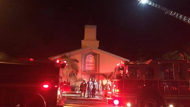 In this photo provided by the St. Lucie Sheriff's Office, firefighters work at the scene of a fire at the Islamic Center of Fort Pierce on Monday, Sept. 12, 2016, in Fort Pierce, Fla.