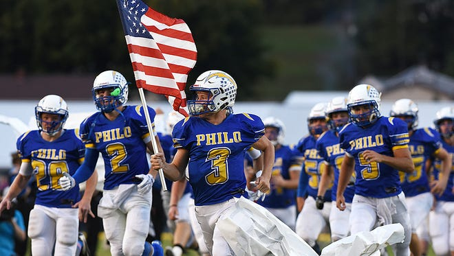 Philo's Dakota Perry sheds a paper banner as he leads the Electrics onto the field against Crooksville. Philo hopes to keep its season alive against Shelby in the Division IV, Region 15 semifinals on Friday,