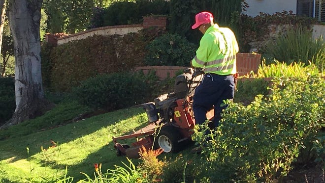 The Oak Park Municipal Advisory Council is seeking residents' input Tuesday night on whether to ask Ventura County to ban weekend gardeners in the upscale, unincorporated community. Gardener Adrian Arellano mows a lawn Friday morning in Oak Park.