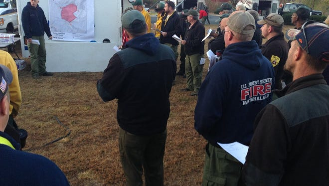 Several firefighters and other personnel met for a morning briefing at a wildfire near Sylva on Wednesday. The Dicks Creek Road fire was 80 percent contained on Thursday October 27, 2016.