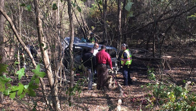 Detectives process the scene of a van that was found burning in the woods off East River Road. A body was found inside.